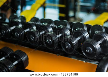 A full set of dumbbells, equipment for increasing strengh and muscle size, weight heavy sports routine, workouts, gyms on a dark blurred background.