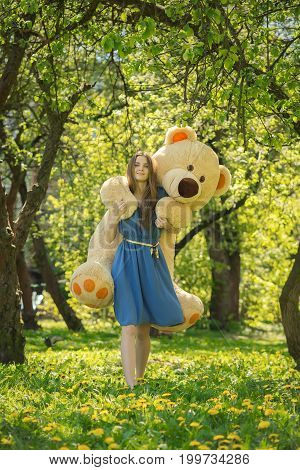 happy girl with big teddy bear walking in spring garden