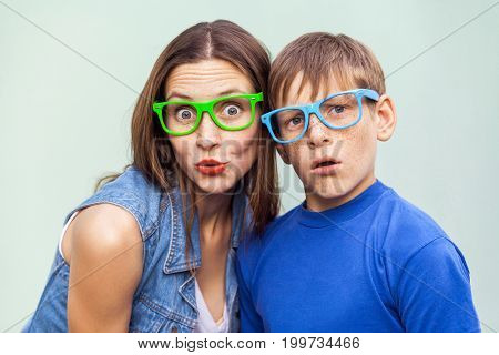Family emotions and feelings. Older sister and her brother with freckles posing over light blue background together on summer time looking at camera with surprised face. Indoor studio shot