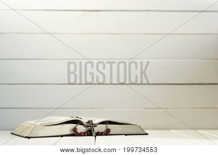 Bible and the crucifix on a white wooden table. Beautiful white wooden background.Religion concept