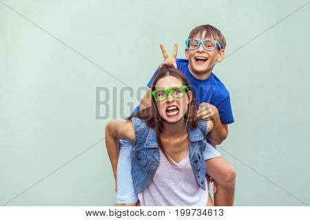 Funny emotions and feelings. The freckled brother climbed up on the back of a older cute sister. Making funny crazy face and looking at camera. Indoor studio shot