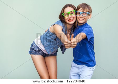 Family emotions and feelings. Older sister and her brother with freckles posing over blue background together looking at camera with toothy smile and thumbs up. Studio shot
