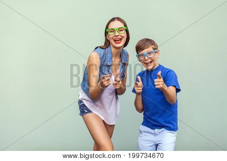 Emotions and feelings. Hey you! The freckled brother and sister in casual t shirts wearing trendy glasses and posing over light green background together. Showing finger at camera and toothy smile. Studio shot