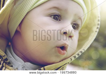 A cute amazed child looks away in the sunny afternoon