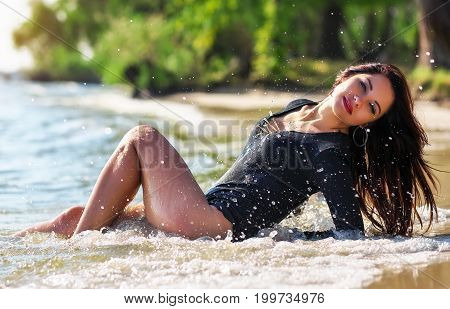 Beautiful attractive sexy girl posing on the beach in sunny hot day