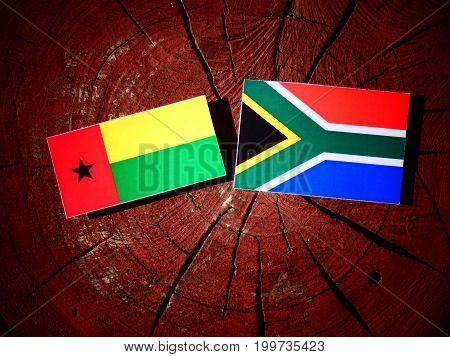 Guinea Bissau Flag With South African Flag On A Tree Stump Isolated