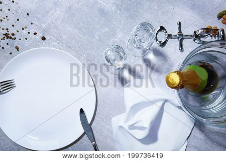 Closeup of a gray table with a white plate, silver corkscrew, green bottle of champagne, different seasonings, snow-white napkin, almonds on a light gray background.