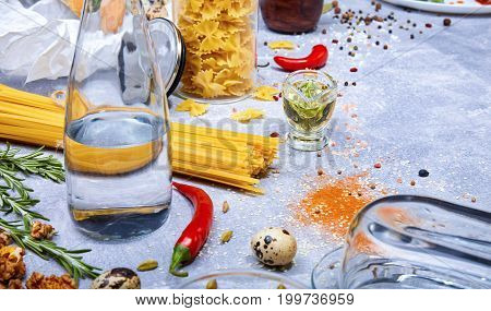 Top view of pasta, red hot chili peppers, little quail eggs, walnuts, a glass bottle, fusilli and different seasonings on a light gray background.