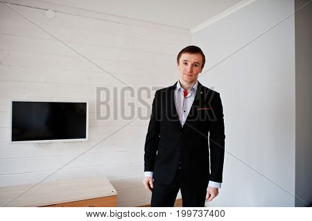 Portrait Of A Handsome Groom Posing In His Wedding Suit In His Big Apartment.