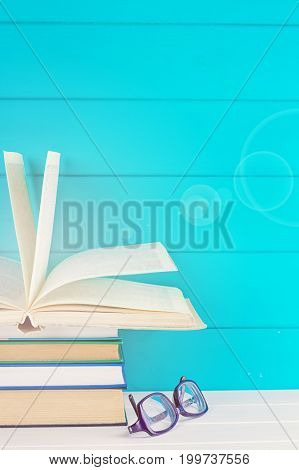 Books stack and glasses on a blue background
