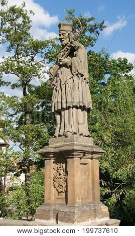 Old statue of Saint Nepomuk on a bridge crossing the Regnitz River, Bamberg, Germany, Europe