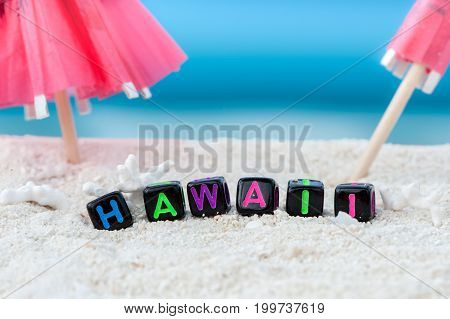 Word Hawaii is made of multicolored letters on snow-white sand against the blue sea. Tourism, rest, resort, sea, sun, beach