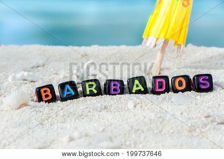Word Barbados is made of multicolored letters on snow-white sand against the blue sea. Tourism, rest, resort, sea, sun, beach