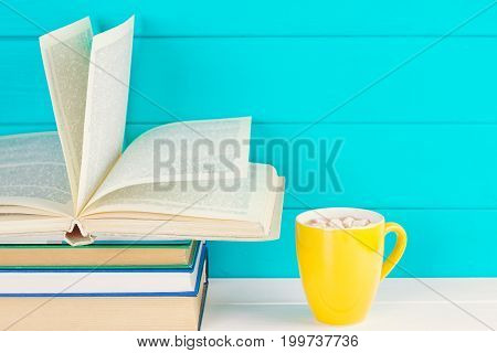 Stack of books on wooden table with a cup of tea. Education background. Copy space for text.