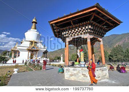 Thimphu Bhutan - November 08 2012: Bhutanese people in traditional dress with Tibetan prayer wheel walking around the National Memorial Chorten praying for blessing in Thimphu Bhutan.