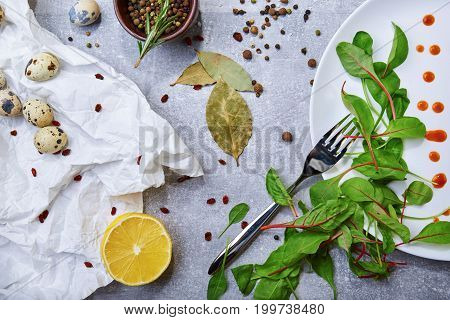 Top view of a white plate with drops of sauce and fresh green leaves, bay leaves, a half of juicy yellow lemon, little speckled quail eggs, a jar with different seasonings on a light gray background.
