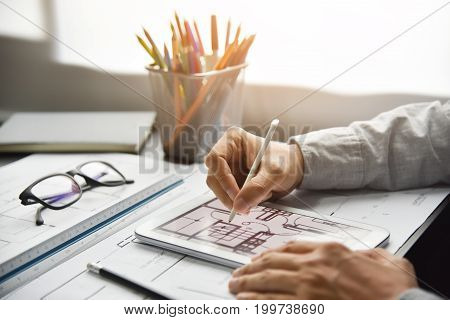 Close up man Designer hands working Interior Architecture drawings with tablet. Office supplies equipment.