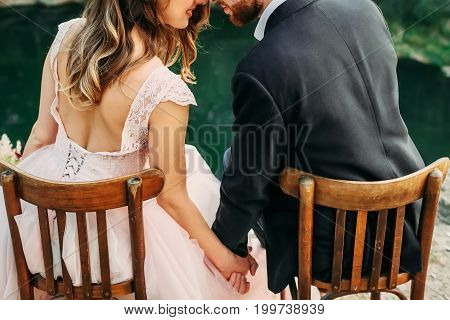Newlyweds Are Sitting At The Edge Of The Canyon And Holding Hands. Bride And Groom Touching Forehead