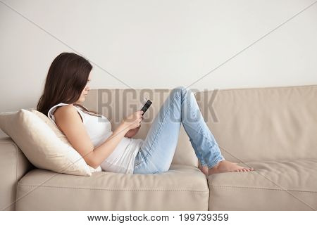 Young woman enjoying bestseller book sitting on couch during free time, teenage student studying textbook before exam, lonely introvert girl spending time at home with literature, reading as hobby