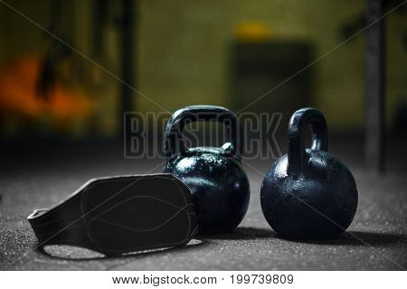 Closeup of two steel black kettlebells with a gray athletic belt on a dark blurred background, cardiovascular, strength and flexibility training, equipment used in the weight lifting sport.