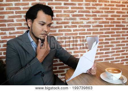Asian businessman are reading documents strictly work during coffee breaks.