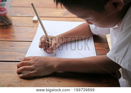 Asian little boy sitting on chair are drawing intently on wooden table with sunlight and white background. Little painter concept.