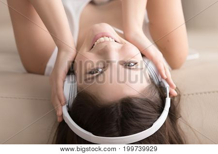 Pretty young woman lying on sofa at home in white headphones, cute teen girl with smiling face listening to audiobook, enjoying favorite mp3 music radio station, close up view, head shot upside down