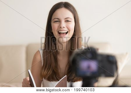 Positive woman talks on digital camera advertising product from catalog when recording videoblog, smiling teen girl makes vlog reviewing bestseller book for internet channel, blogger streaming online