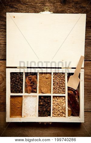 Assortment Of Spices In Wooden Box On Old Wooden Table