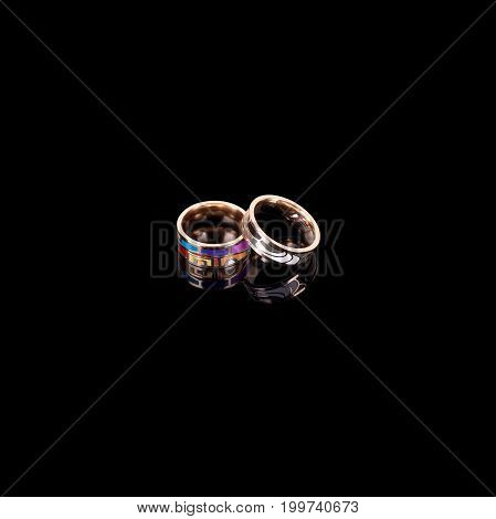 Gold rings with enamel on black background