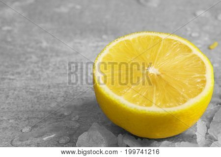 Close-up of a half of juicy, sappy, yellow lemon with pieces of ice, drops of water, refreshing citruses for summer healthy cocktails on a light gray background. Citrus fruits. A juicy bright yellow lemon.