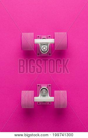white longboard trucks and pink wheels. longboard trucks and wheels on deep pink background. longboard trucks and wheels with copy space. top view of pink longboard trucks