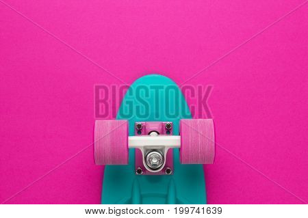plastic mini cruiser board on deep pink background. top view of plastic cruiser board. shot of mini cruiser board with copy space. shot of nose part of light sea green mini cruiser board
