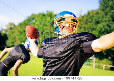 An american football player passing the ball to his team mate