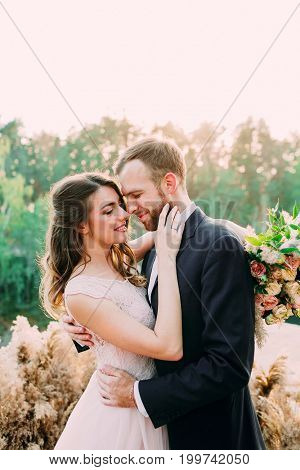 Portrait Of Affectionate Newlyweds Touching By Their Noses. Bride And Groom Posing On Nature. Weddin