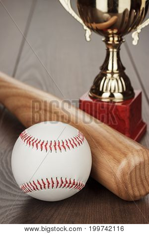 golden trophy cup and baseball bat and ball on the wooden table