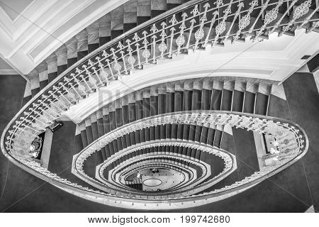 Spiral stairs black and white - Monochrome image of spiral stairways made from marble with a red carpet and an elegant railing view from above