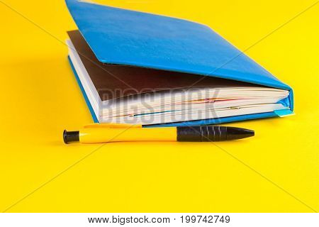 blue Daily planner with colored bookmarks. yellow background.