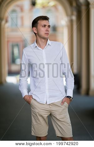 A beautiful young man with brown hair and snow-white shirt holds hands in pockets of his beige breeches and looks in the distance on a light blurred background, concept, dating, business, studying.