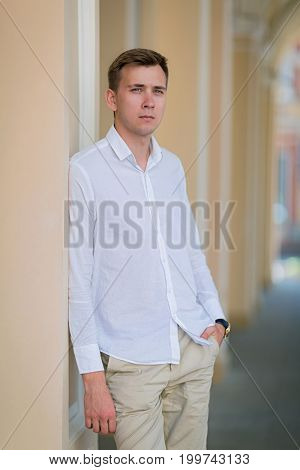 A beautiful guy in a snow-white shirt holds his arm in a pocket of light ecru pants and looks in a distance on a light blurred background, concept, dating, business, studying.