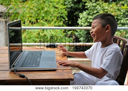 Asian little boy sitting played laptop with happily.