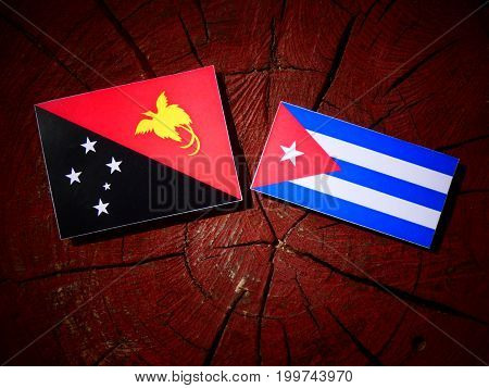 Papua New Guinea Flag With Cuban Flag On A Tree Stump Isolated