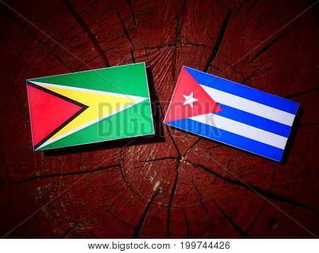 Guyana Flag With Cuban Flag On A Tree Stump Isolated