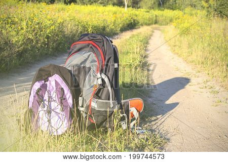 Travel backpack on the background of scenic trails along the rapeseed fields summer holiday the concept of travel and active lifestyle
