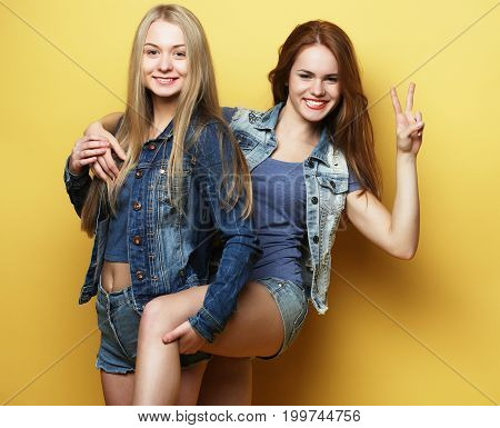 people, teens and friendship concept - happy smiling pretty teenage girls or friends hugging and showing peace hand sign over yellow background