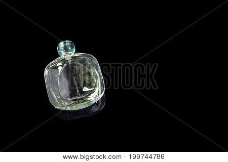Perfume bottle with reflection on black background. Perfumery, cosmetics. Copyspace for text