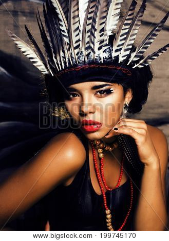 young pretty woman with make up like North American indian, feather in hair, fashion halloween concept creative close up