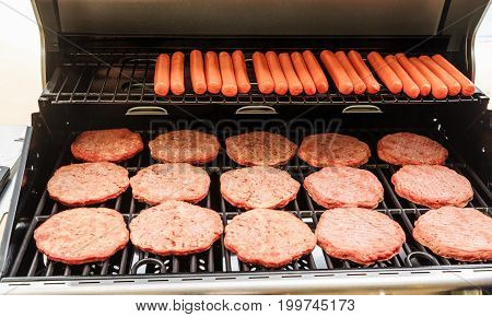Hamburger Patties and Hot Dogs Cooking on a New Gas Grill