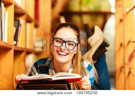 Education school concept. Clever female student girl in blue glasses lying on floor in college library with stack books reading. Indoor