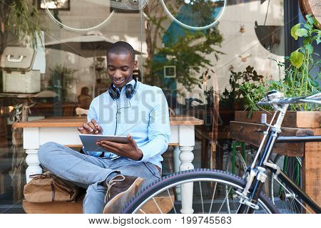 Stylish young African man working on a digital tablet while sitting next to his bicycle at a trendy sidewalk cafe